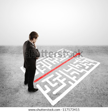 businessman in front of labyrinth with arrow - stock photo