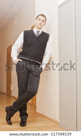 Businessman in full-length standing against a wall in a corridor