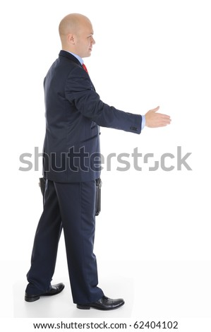 Businessman in full-length stretches out his hand for a handshake. Isolated on white background