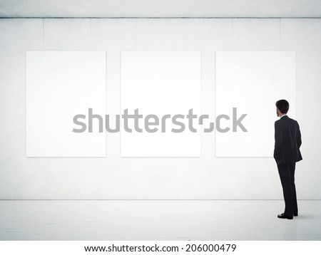 Businessman in gallery room looking at empty frames - stock photo