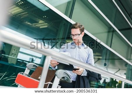 Businessman in glasses reading a customs declaration at the airport - stock photo