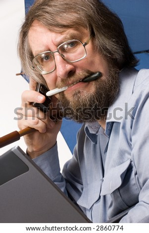 businessman in glasses with notebook, phone mobile, umbrella in his hands and pen in his teeth - stock photo