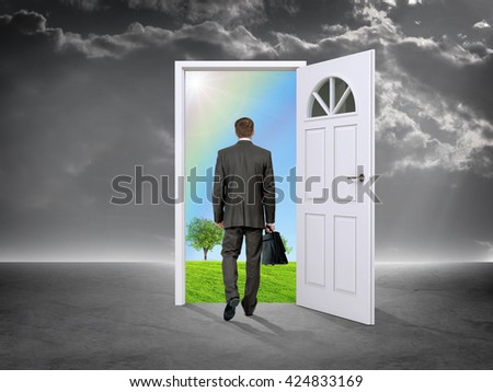 Businessman in grey room with door in nature, rear view