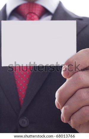 Businessman in grey suit and a blue shirt with a red power tie, shows business card with copy space, shallow dept of field - stock photo