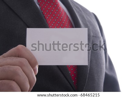 Businessman in grey suit and a blue shirt with a red power tie, shows professional business card with copy space, shallow dept of field - stock photo