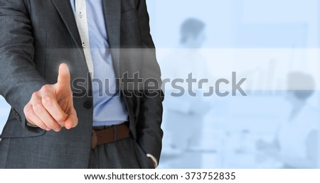 Businessman in grey suit pointing against blue background - stock photo