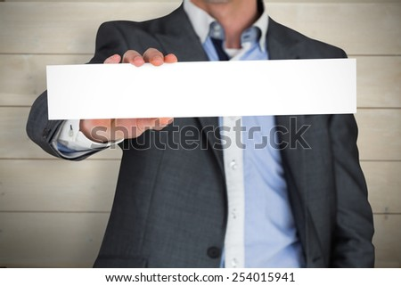 Businessman in grey suit showing card against bleached wooden planks background - stock photo