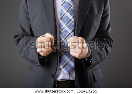 businessman in handcuffs arrested isolated on grey background - stock photo