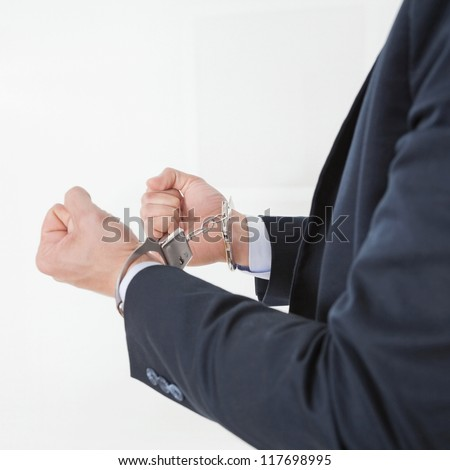 Businessman in handcuffs getting arrested for white collar crimes - stock photo