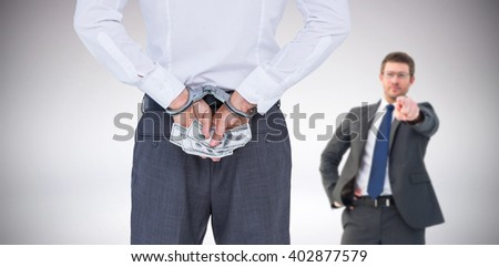 Businessman in handcuffs holding bribe against grey background - stock photo