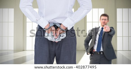 Businessman in handcuffs holding bribe against room with windows - stock photo