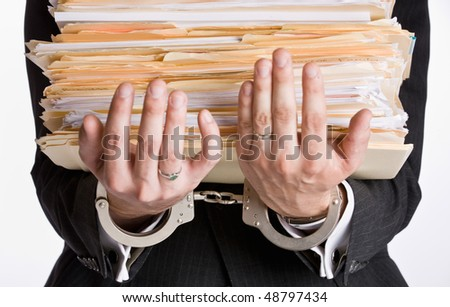 Businessman in handcuffs holding file folders - stock photo