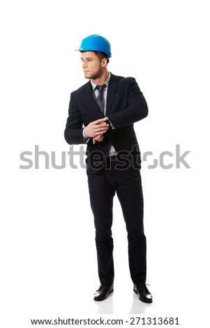 Businessman in hard hat checking time on his wrist watch. - stock photo