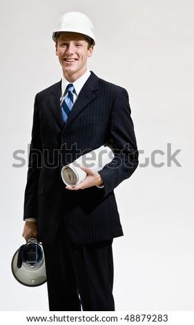Businessman in hard-hat holding blueprints - stock photo