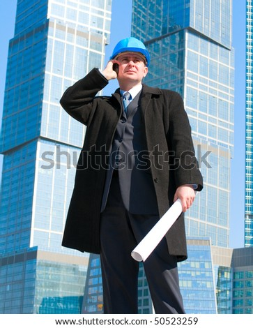 Businessman in hard hat talking on cell phone and holding drawing in his hand,on skyscrapers background - stock photo