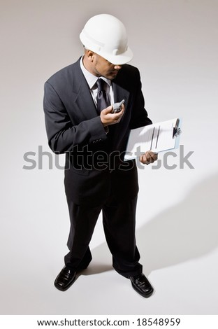 Businessman in hard-hat with walkie-talkie and clipboard