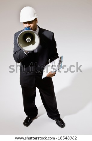 Businessman in hard-hat with walkie-talkie, clipboard and shouting instructions into megaphone