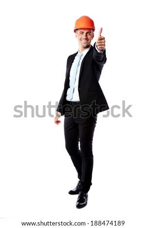 Businessman in helmet giving thumbs up over white background - stock photo