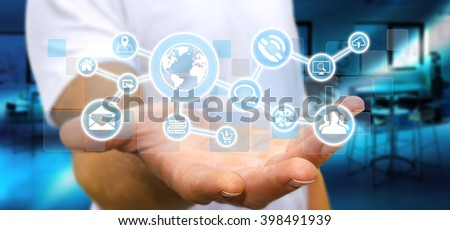 Businessman in his office holding a digital tactile screen web network with web icons - stock photo