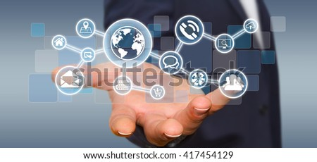 Businessman in his office holding a digital tactile screen web network with web icons