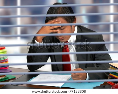Businessman in his office reading documents - stock photo