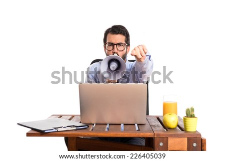 Businessman in his office shouting by megaphone - stock photo