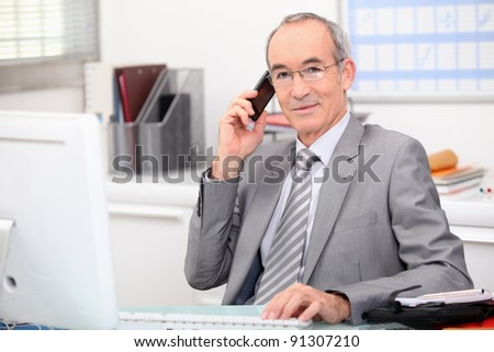 businessman in his office taking a call - stock photo