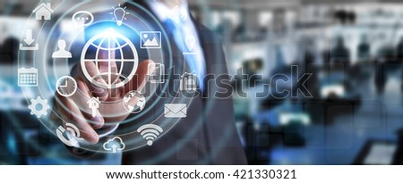 Businessman in his office using a digital tactile screen interface with web icons