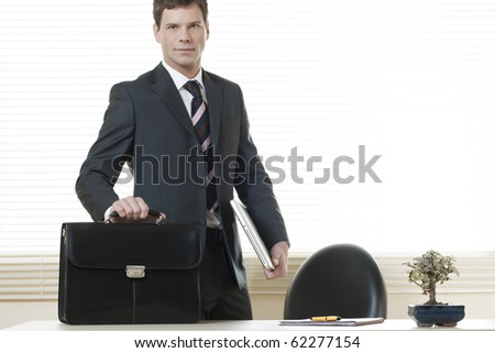 Businessman in his office with briefcase - stock photo