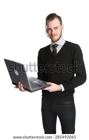 Businessman in his 20s in a shirt and tie wearing a headset and holding a laptop computer. White background.