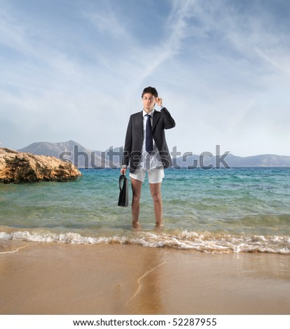 Businessman in jacket and boxers standing on the sand of a beach - stock photo