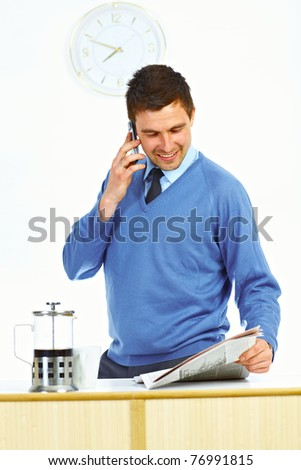 Businessman in kitchen talking by mobile phone, reading newspaper and smiling - stock photo