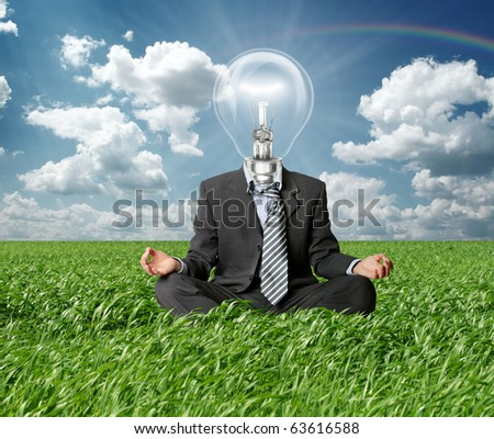 businessman in lotus pose and lamp-head in grass in green grass on blue summer sky - stock photo