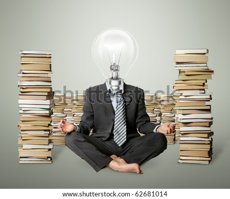 businessman in lotus pose and lamp-head with many books near - stock photo