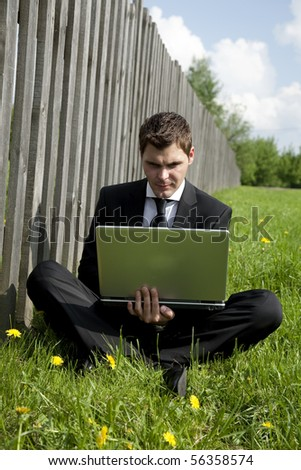 businessman in lotus pose working on laptop in country - stock photo