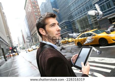 Businessman in Manhattan using digital tablet in the street - stock photo