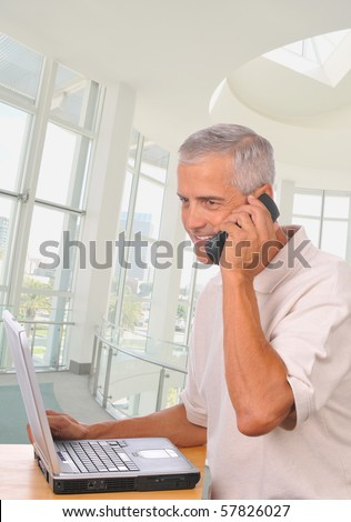 Businessman in modern office setting talking on his cell phone and seated at his laptop computer.