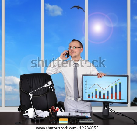 businessman in office and holding monitor with chart - stock photo