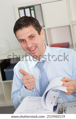Businessman in Office Flipping Through Binder Giving Thumbs Up and Looking at Camera