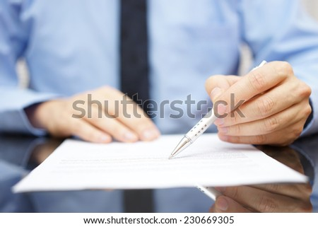 businessman in office is analyzing document - stock photo