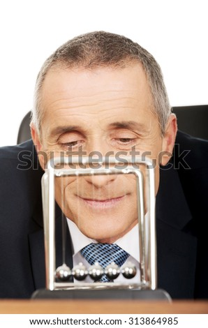 Businessman in office playing with newton balls. - stock photo