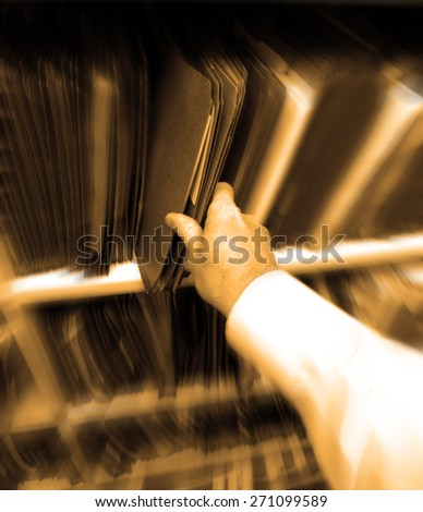 Businessman in office pulling file folder of documents off shelf - stock photo
