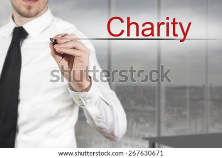 businessman in office room writing charity in the air - stock photo
