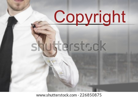 businessman in office room writing copyright in the air - stock photo