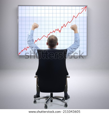 Businessman in office sat on a chair with arms raised in front of a successful growth chart - stock photo