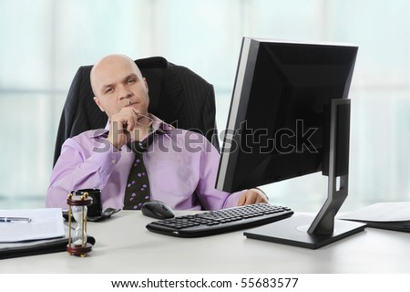 Businessman in office sitting before a computer. - stock photo