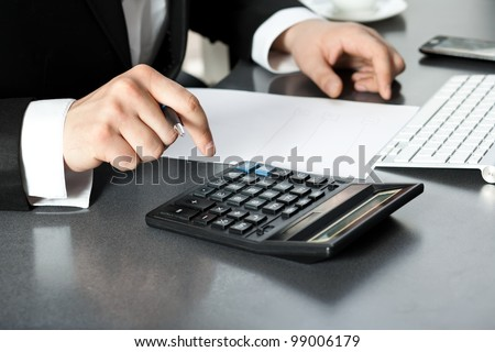 Businessman in office sitting by computer and finds the calculator - stock photo