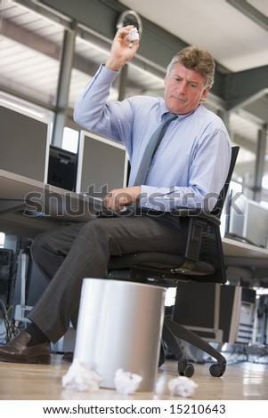 Businessman in office space throwing garbage in bin - stock photo