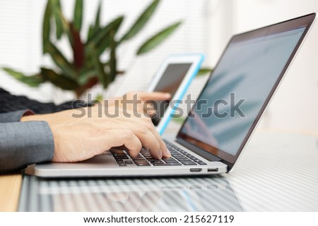 businessman in office  typing on keyboard with businesswoman using tablet pc in background - stock photo