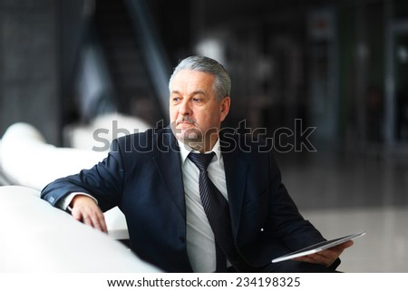 businessman in office with the tablet sits and works - stock photo